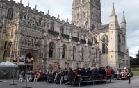 Audience watching 'Coram Boy' with Gloucester Cathedral in the background