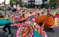 Carnival dancers parading through Tilbury, Thurrock adorned in brightly coloured garments accented with a keyboard pattern