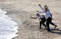 Photo of three woman skimming stones on a beach