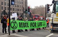 Protesters stopping traffic holding a 'Rebel for life' banner