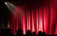 Photo of a silhouette of an audience facing a red stage curtain