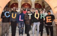 "Photo of a group of people holding individual letters to spell out ""cuture"""