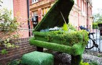 Photo of a grand piano as a garden feature, covered in plants.