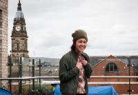 Photo of female actor on rooftop with church spire behind