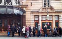 Photo of people queuing outside the London Coliseum