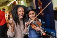 Photo of musician with young girl playing violin