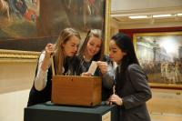 Photo of three girls in gallery standing over a box