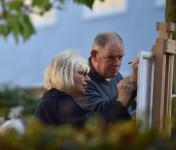 Photo of two people painting at an easel