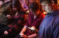 Photo of a group of people looking at their phones