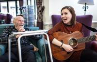 a woman seated playing guitar to an elderly gentleman seated witha zimmer frame in the foreground
