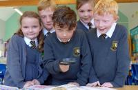 Photo of schoolchildren looking at books with microscope