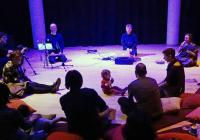 Photo of baby in centre stage with musicians