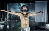 Photo of a bearded actor, clad only in stained briefs, arms outstretched