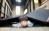 Photo of a boy under a big black sheet