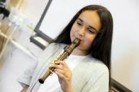 Photo of a girl playing a one-handed recorder