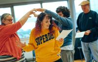 A photo of people dancing and a woman reading from a sheet