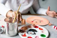 A child's hand pouring paint into a palette