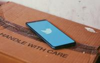 Twitter loading screen on a phone resting on a cardboard box