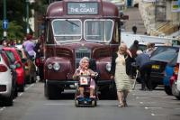 Photo of old bus, scooter and mayor on parade