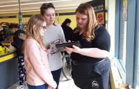Photo of three people looking at ipad in supermarket