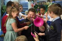 Photo of musician with pink trombone surrounded by school children