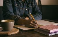 Black female sitting at a desk, writing with a pencil. Coffee cup and saucer in the foreground