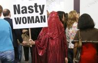 Photo of woman in red shador with banner 'Nasty Woman'