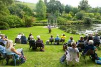 People sitting in a garden watching a speaker socially distanced