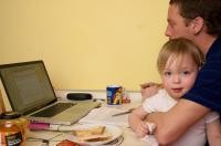 Photo of a man working from home with a child