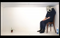 Man in a mask sitting in a low, celingless room
