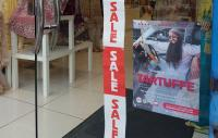 Image of a shop front with a sale banner and promotional theatre performance poster