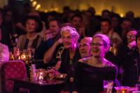 Audience sitting at tables with drinks