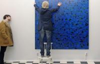Photo of man hanging painting