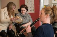 Image of clarinetist & young woman in wheelchair with tambourine