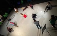 A group of performers lying on stage distanced from one another