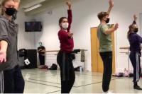 Four students performing dance in a class wearing masks