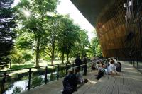 Photo of people on terrace overlooking river and park