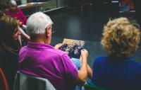 photo over the shoulder of an older gentleman sitting down who is looking at a photograph