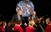 The Prime Minister and Sir David Attenborough sitting in front a picture of the globe, answering questions from pupils from Barnes Primary School and John Betts Primary School