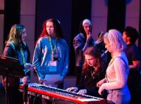 Photo of young people grouped round a keyboard