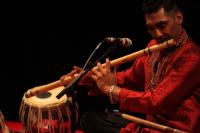 Photo of a man playing the bansuri flute