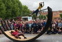 Photo of street art, woman hoisted on seesaw
