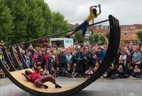 Photo of street art, woman hoisted on seesaw