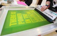 "screenprinting a poster which says ""There is power in the unity of humanity"""