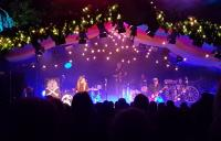 A photo of band performing on a brightly lit stage