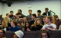 Students sitting in a lecture theatre chatting