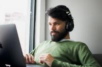 A man sitting with a macbook on his lap while wearing headphones