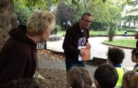 Photo of a man and woman leading outdoor workshop about trees to young children