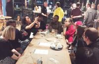 Photo of people sitting round a long table