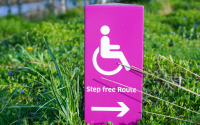 a sign with a logo of a person in a wheelchair, signalling access to a step free route